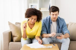 Couple working out finances | Featured image for Budgeting for Your Home Loan: Tracking Your Expenditure blog