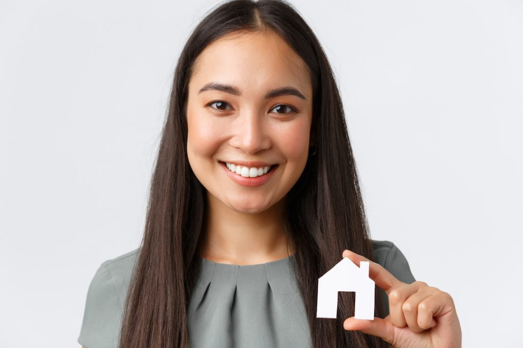 Woman Holding Up Home Cut-Out | Featured Image For new govenor same cash rate blog