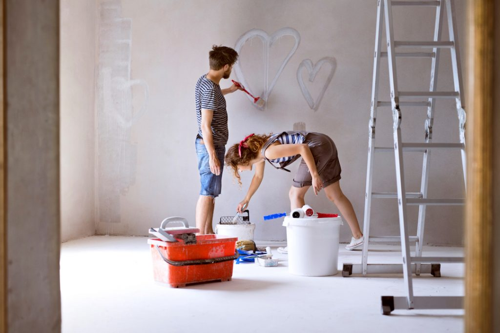 Couple painting hearts on the wall in their house | Featured image for 3 Tips On Buying a Fixer Upper blog