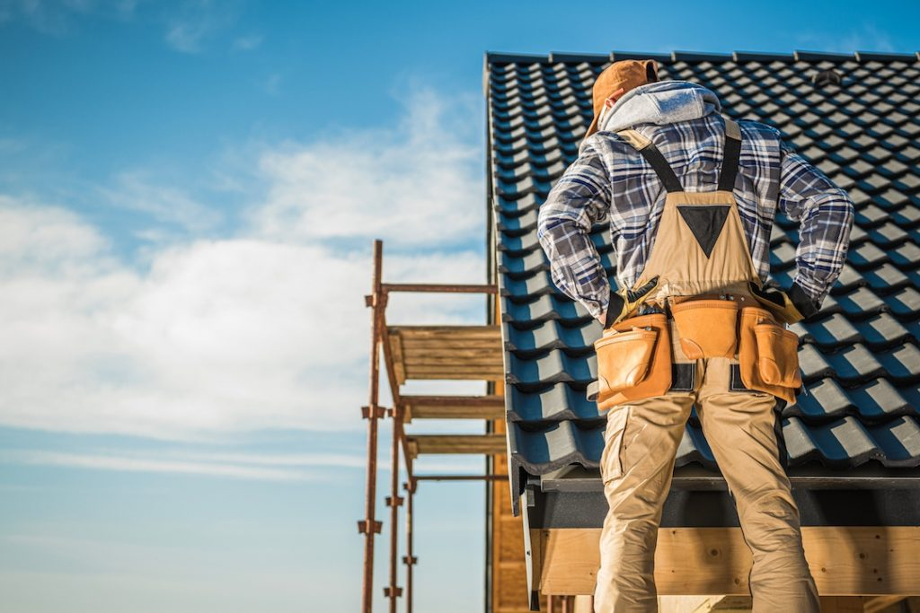 tradie standing on roof | Featured image for What's the Key to Quick Capital Gains? blog