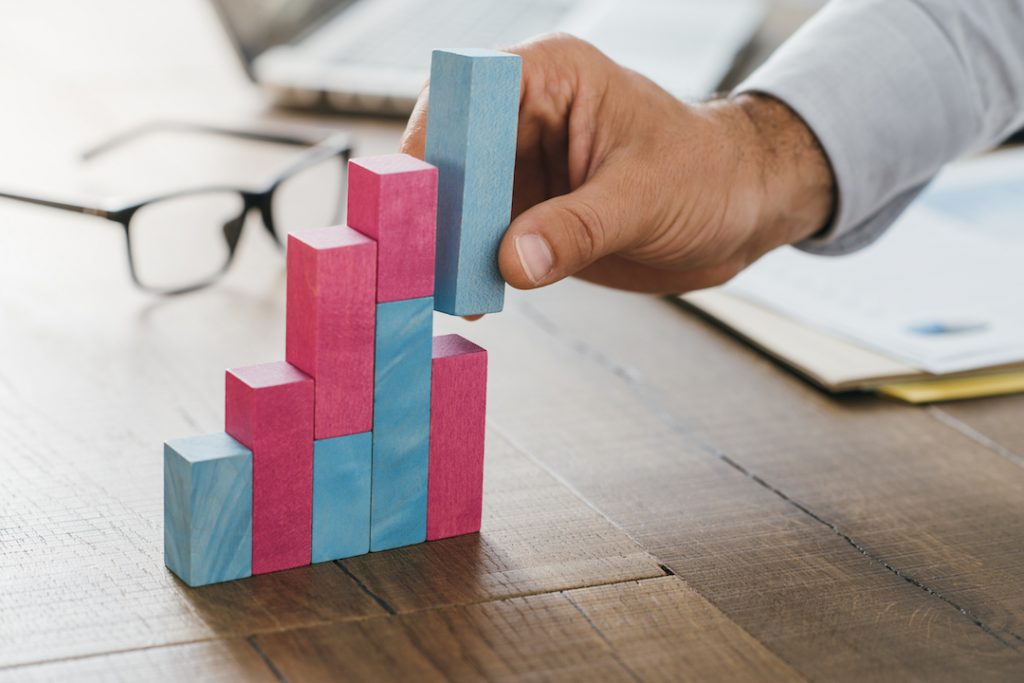 man using building blocks to make a growing graph   Featured image for Start the Road to Riches with these Financial Goals blog