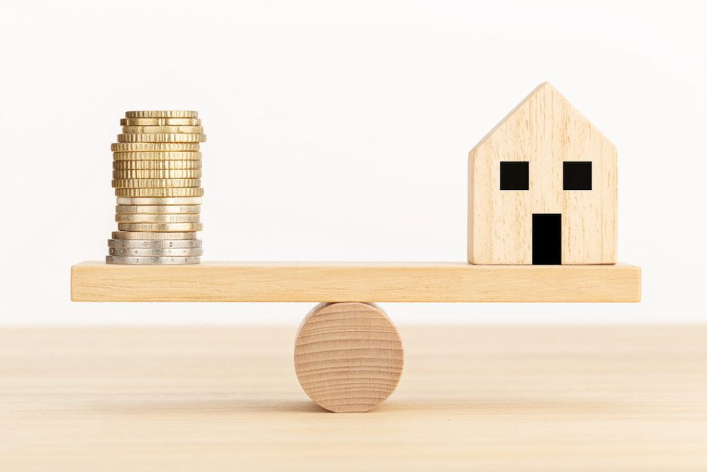 balancing a stack of cooins and a home | Featured image for Is an Interest Only Loan Right for You? blog