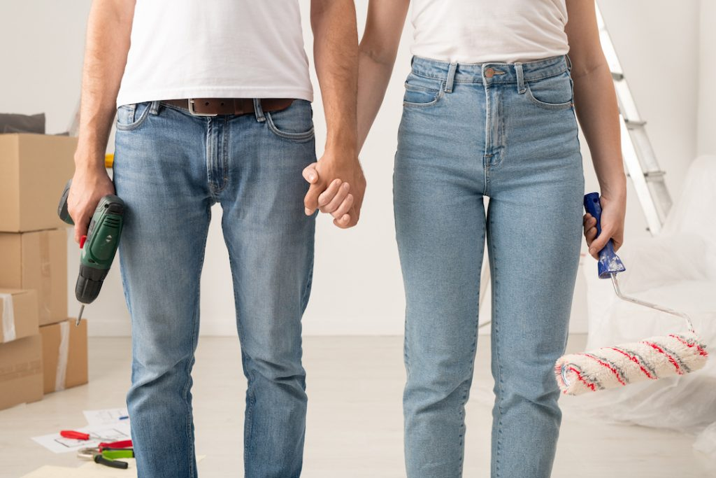 Couple in jeans holding hands while also holding tools | FEatured image for Renovating Your Home Can Add Value and Quality of Life blog