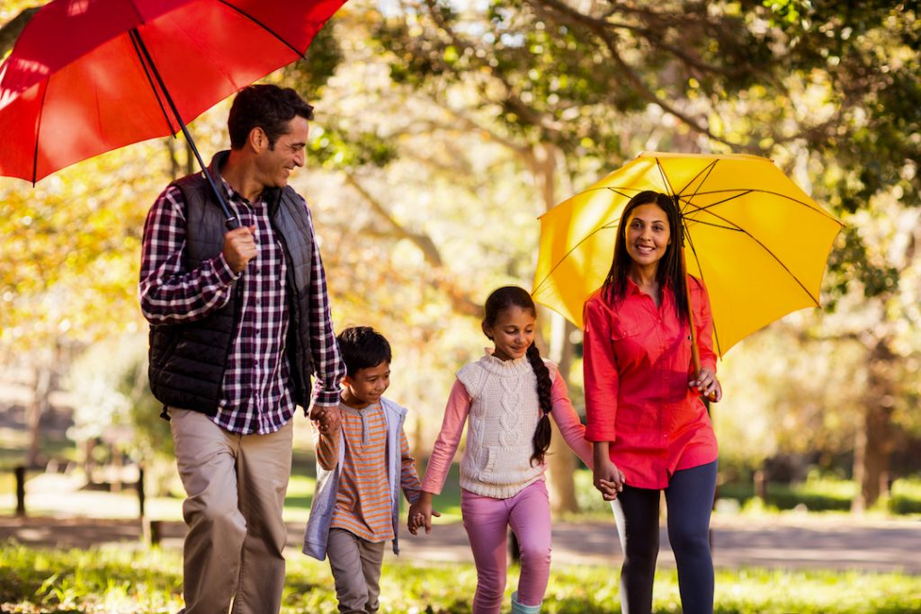 family walking through park with umbrellas | Featured image for Is a Split-rate Home Loan the Best Option for You? blog