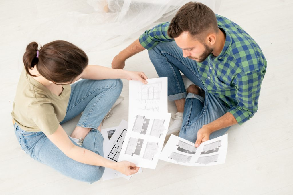 couple looking at house plans | Featured image for Renovating Your Home Without Breaking the Bank blog
