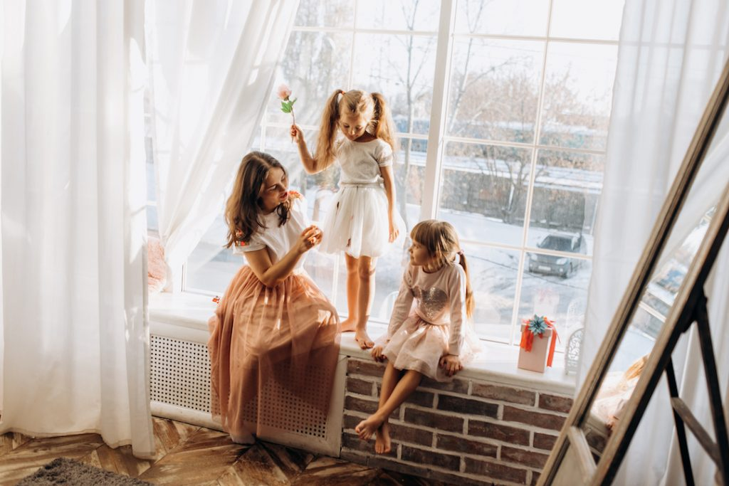 Mother and daughters playing by the window | Featured Image For Why Winter is a Good Time to Buy Property blog