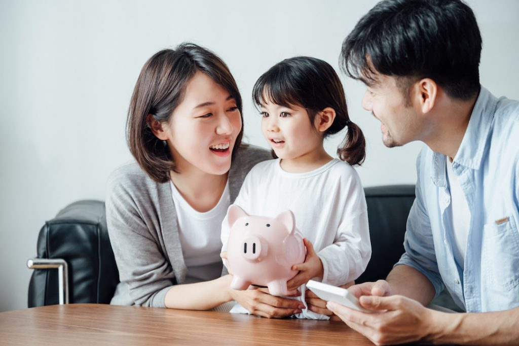 family and daughter smiling at piggy bank | Featured Image For Saving as Much as Possible to Make a Deposit on a Home blog