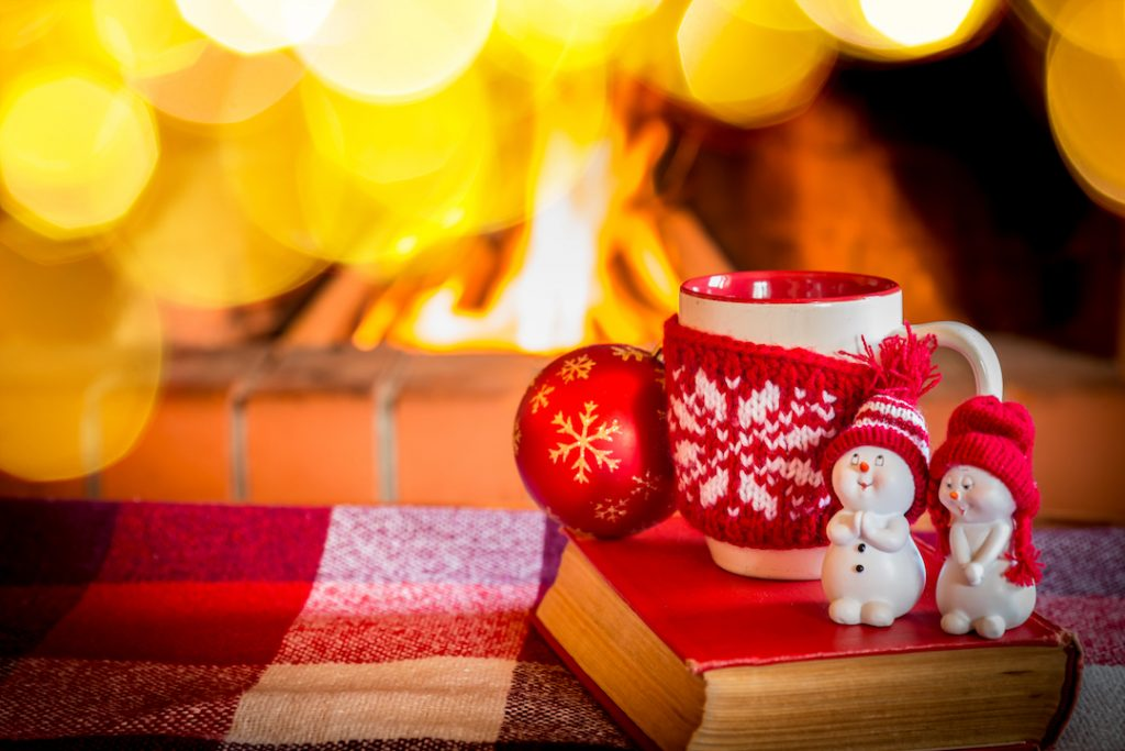 christmas mug infront of lit fireplace | Featured Image For Cash Rate Remains on Hold for Christmas blog
