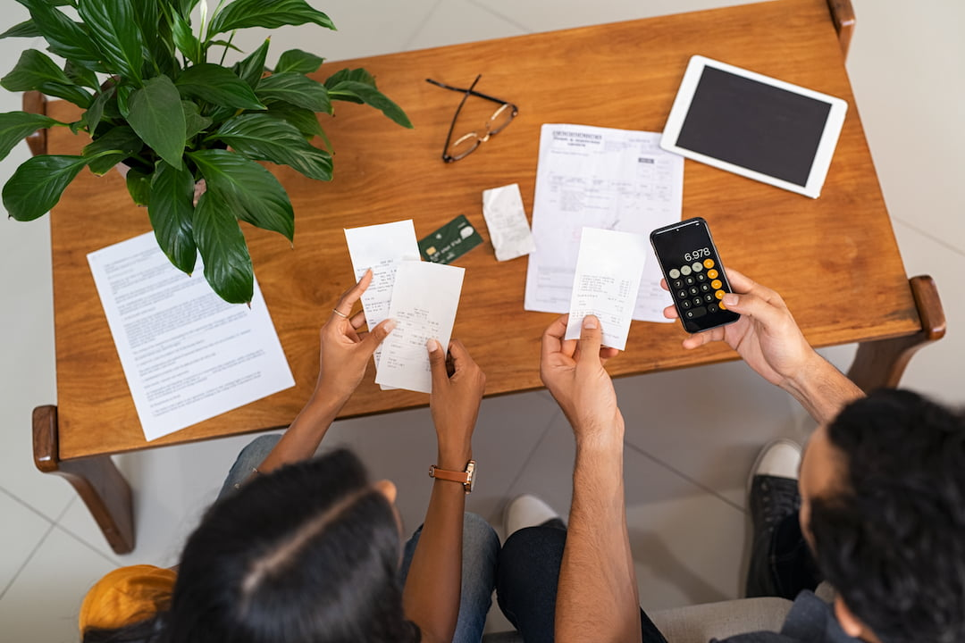 Couple working out finances on calculator | Featured Image For Our Tips on How to Get Your Finances Back on Track blog