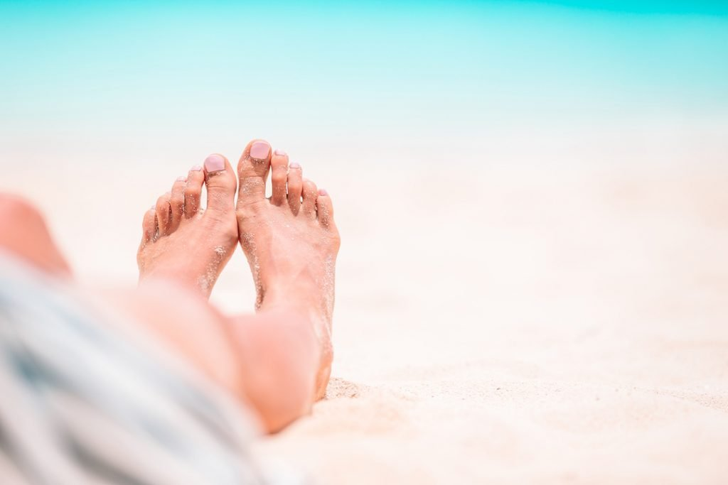 bare feet in the sand | Featured Image For Popular Holiday Spots to Invest In blog