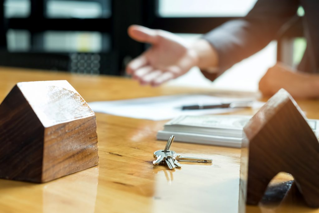 keys waiting to be given over with a handshake | Featured Image For How Much Money Do You Need to Start Investing in Property? blog