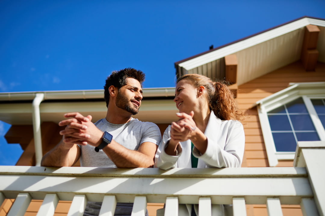 couple leaning of balcony talking | Featured Image For What is Negative Gearing for Property Investment? blog