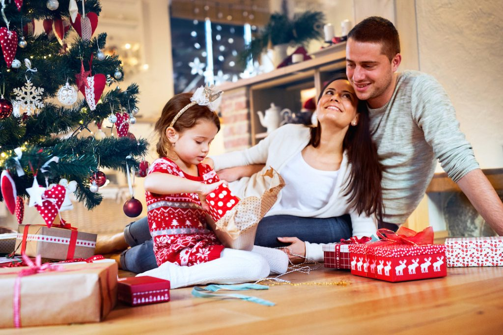 family watching daughter open presents | Featured Image For How You Can Protect Your Credit Rating This Christmas blog