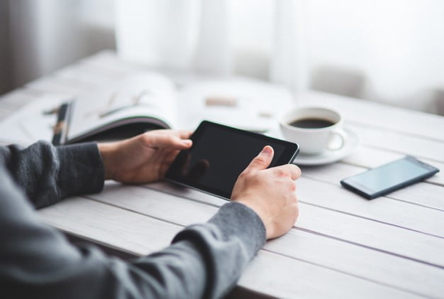 Man sitting at table holding ipad | Complimentary Image For Reasons Why You Should Refinance Your Home Loan blog