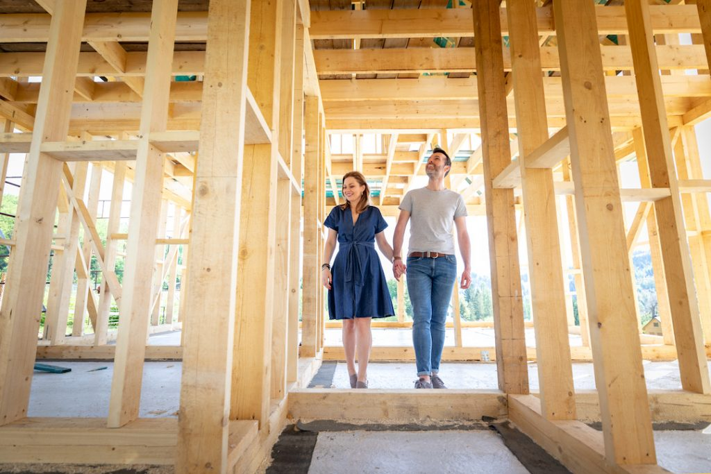 couple walking through home construction frames | Featured Image For Self-Employed People Have Happy Lives - But Can They Buy Houses? blog