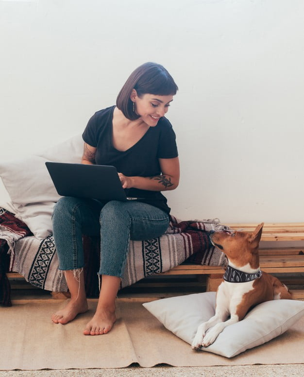 Woman on laptop talking to dog | Featured Image for Reasons Why You Should Refinance Your Home Loan blog
