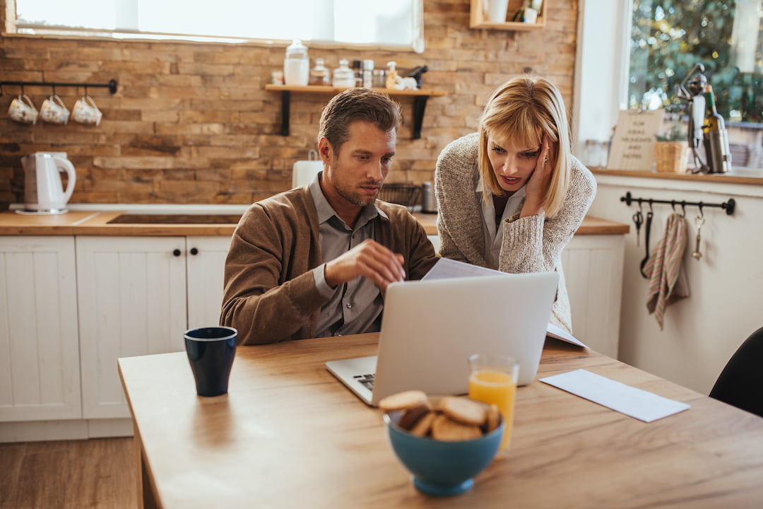 Couple paying bills online at home   Featured image for 3 Ways to Save on Utility Bills blog