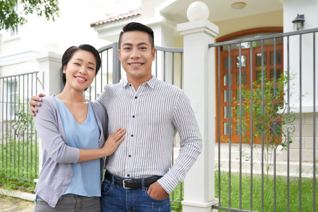 Couple posing for photo infront of house | Featured image for Love and Mortgages: Buying a Home with a Partner blog