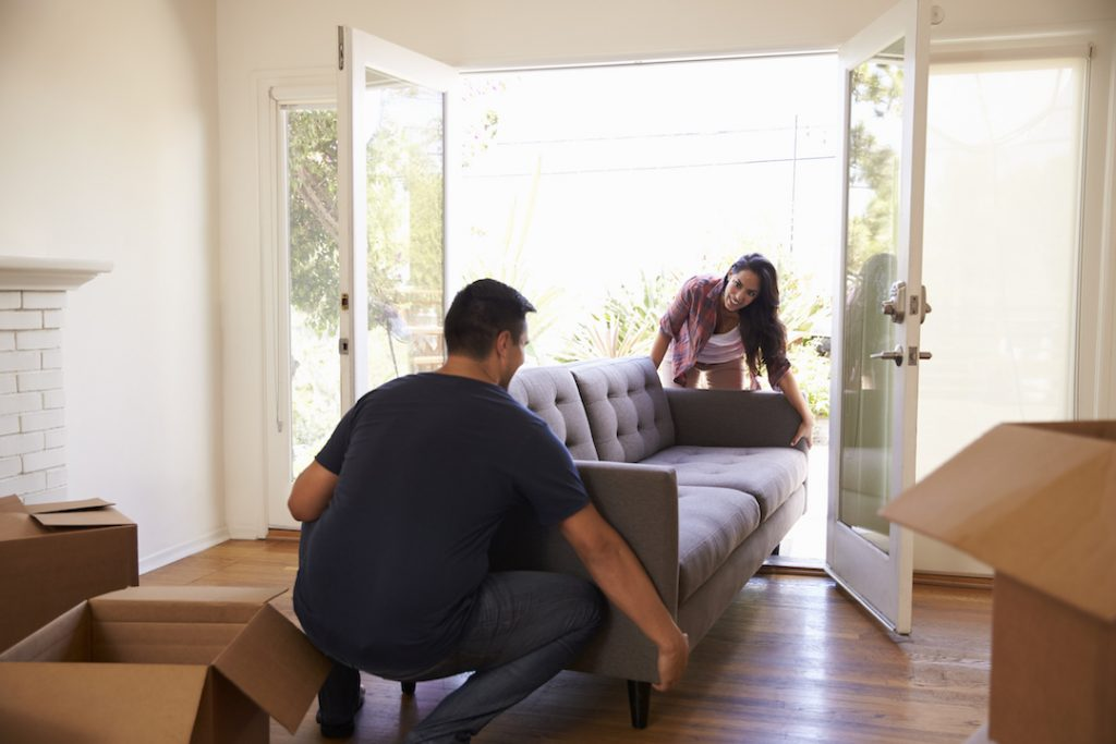 Couple Unloading Couch | Featured Image for Can It Be Cheaper To Buy Than Rent blog