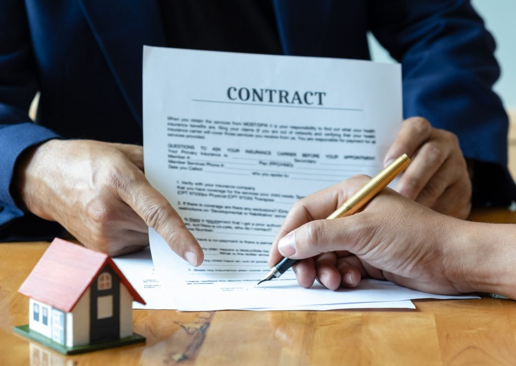 Person signing contract | Featured image for 3 Questions to Ask Yourself Before Refinancing Your Loan blog