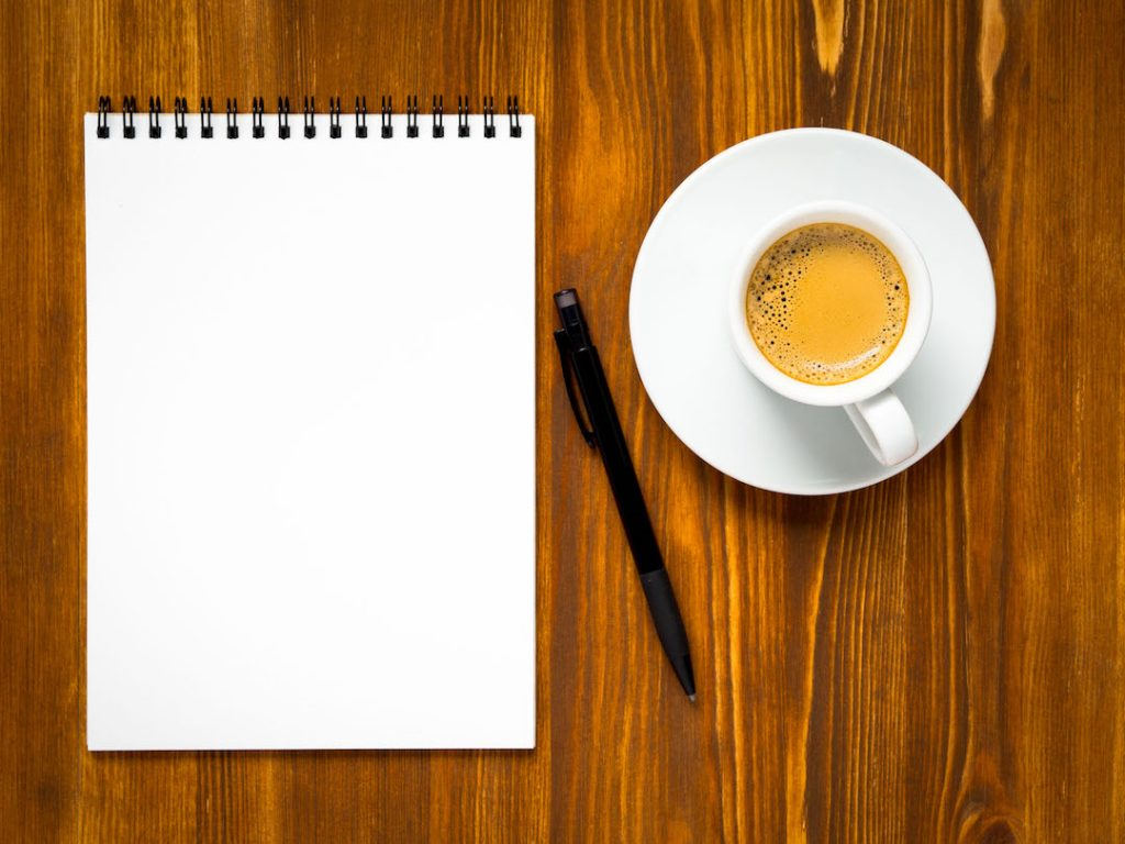 Coffee mug and empty note-pad | Featured image for What You Need to do Before Investing in Property blog