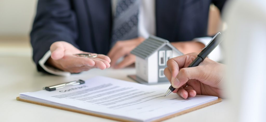 Bank vs Mortgage Broker - Where to Get a Mortgage From Blog Featured Image - Man Signing a Contract on a Home Loan for a Home Purchase