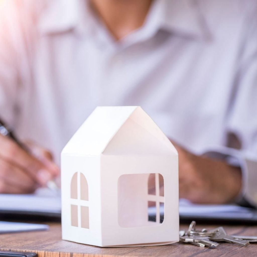 Designer makes notes with a small house on table | Featured image for steps for buying a house blog.