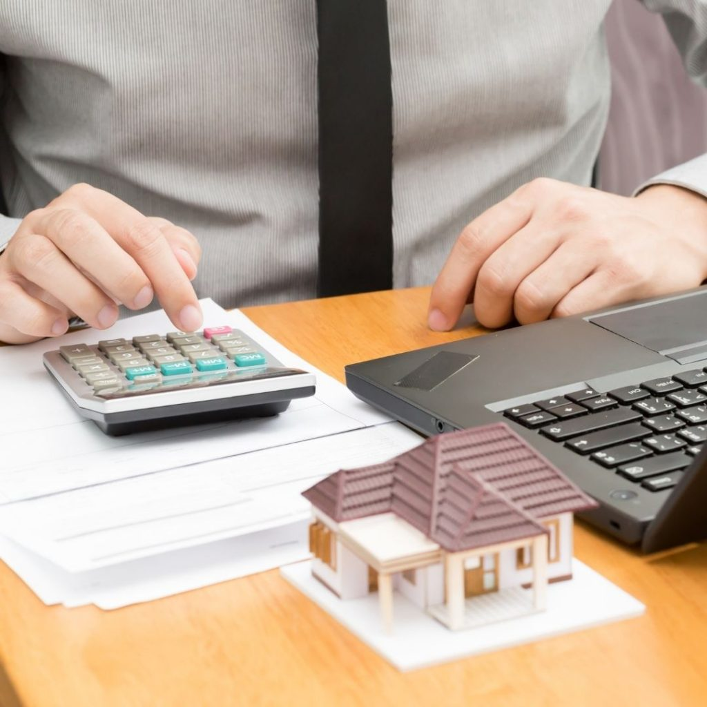 Mortgage broker using a calculator and laptop | Featured image for Mortgage Switching blog.