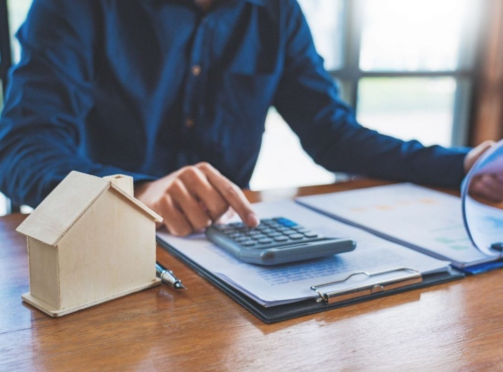Mortgage broker using a calculator and contract | Featured image Real Estate as Part of Retirement Portfolio blog.