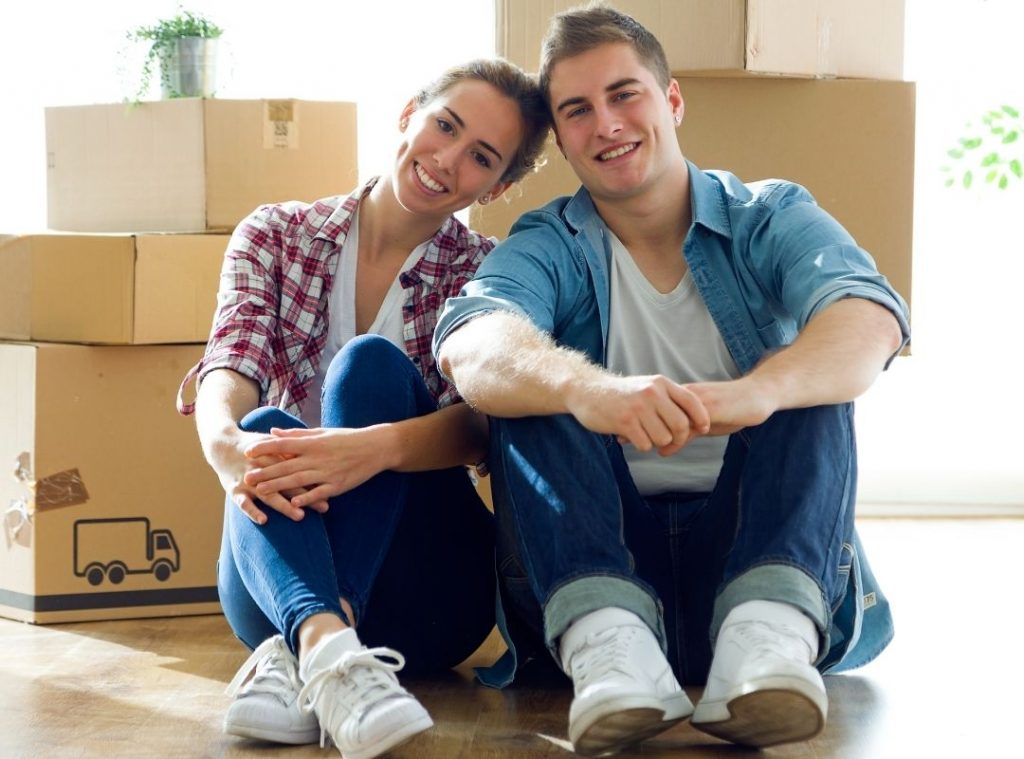 Couple smiling with boxes in the background   Featured image First Home Buyer FAQ blog.
