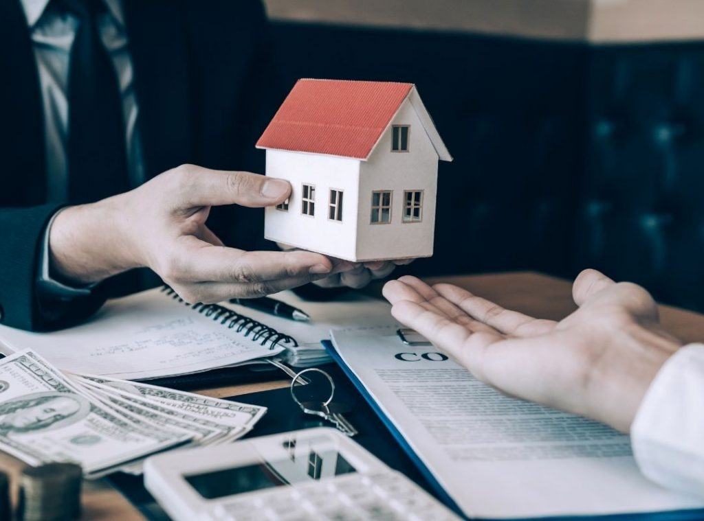 Mortgage broker handing a small house to a house buyer | Featured image for How to Win a Property Auction
